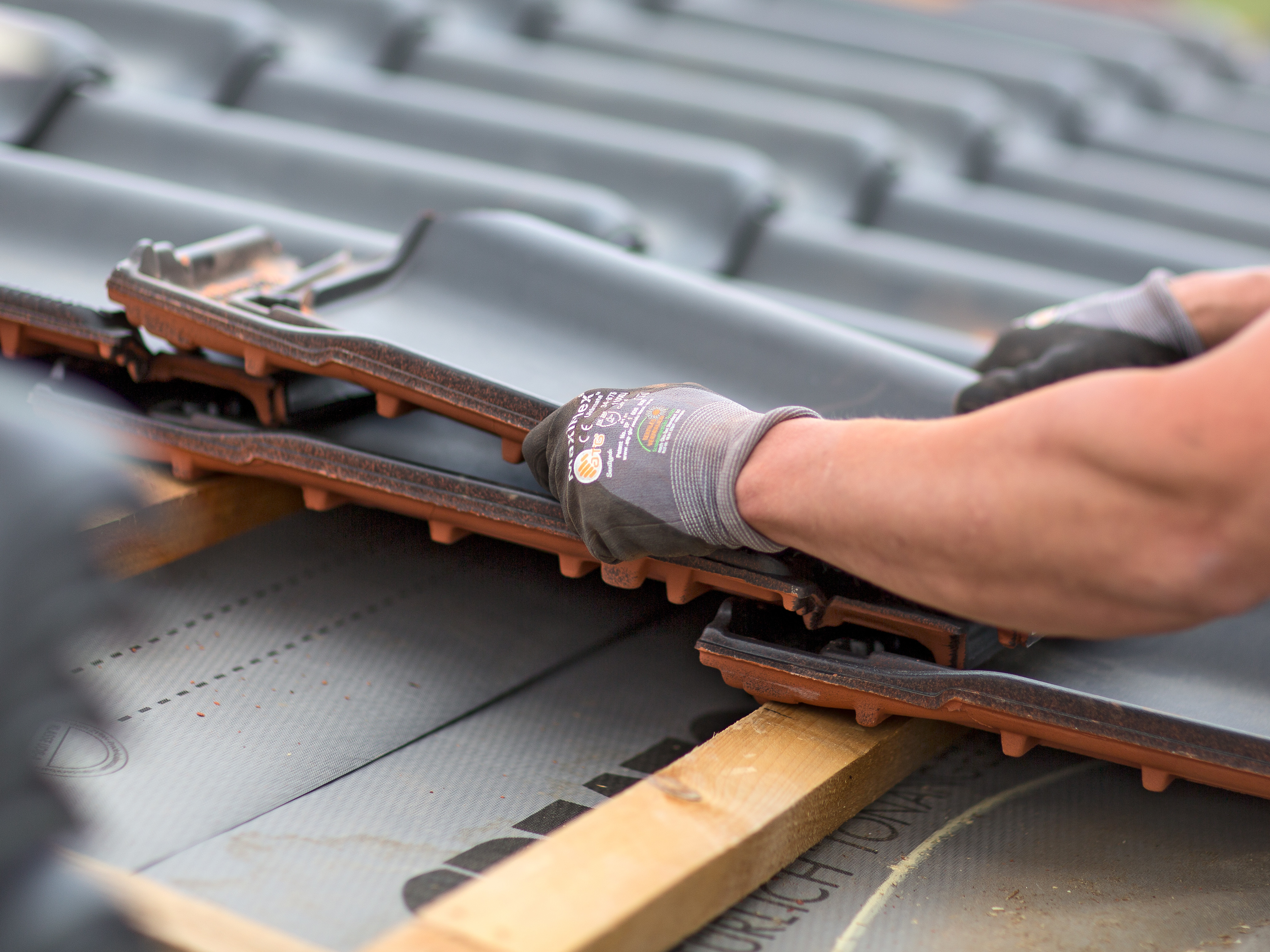 Roofer covers tile on the roof